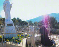 On Apparition Hill in Medjugorje, Father David, the miracle working Capuchin priest, who has Stigmata wounds on his hands and feet, WILL OFFER 365 MASSES FOR YOU AND YOUR FAMILY AND FOR ALL OF YOUR INTENTIONS, is shown here in front of the Blessed Virgin Mary Statue.